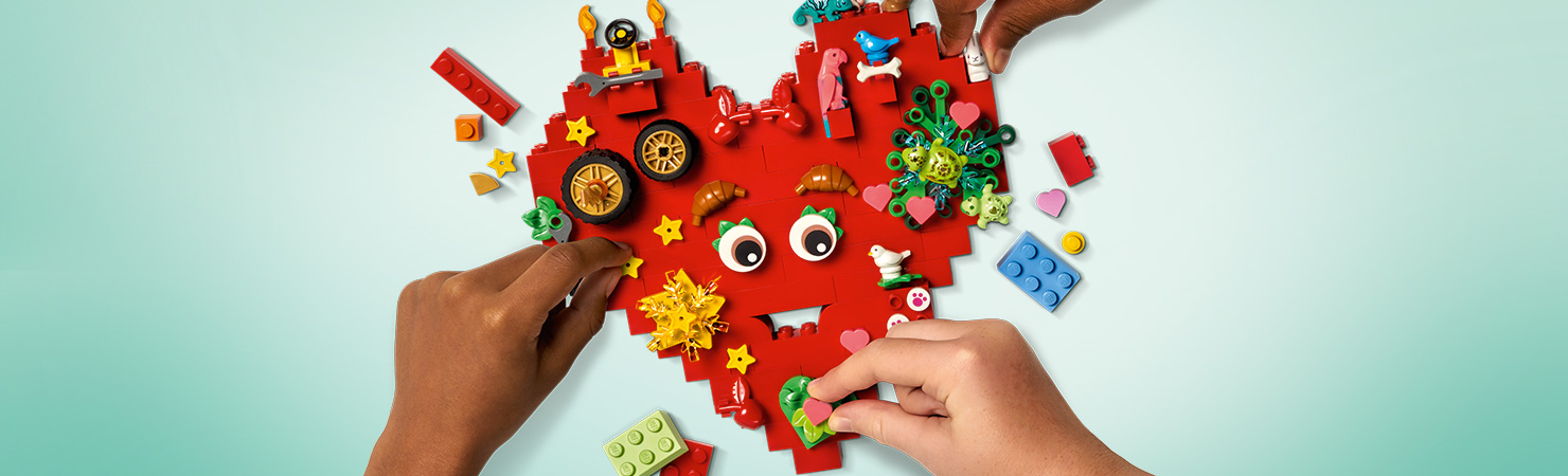 A heart LEGO creation being built by 3 hands